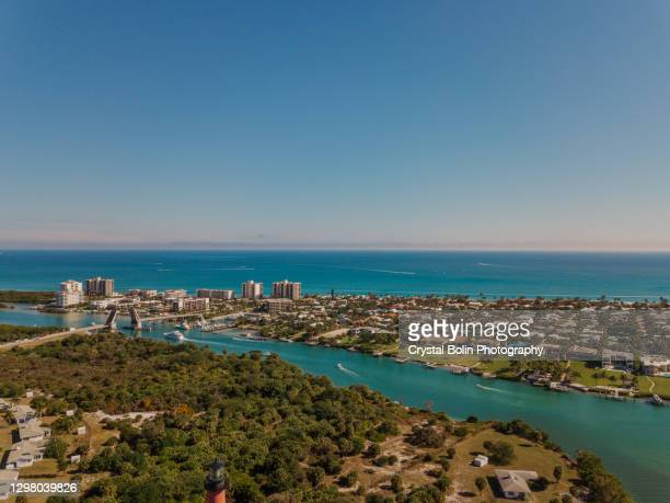weekend aerial views of boats moving on the teal ocean water & the jupiter lighthouse in jupiter beach, florida at mid-day in january of 2021 - jupiter florida stock pictures, royalty-free photos & images