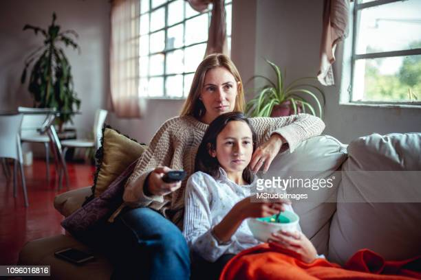 weekend at home. - family watching tv stock pictures, royalty-free photos & images