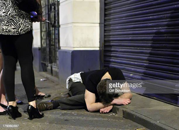 Weekend drinking in Belfast. A man lies in the street after leaving a nightclub which offers cut-price drinks as part of a promotion to attract more...