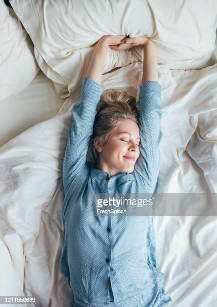 wochenendmorgen: happy blonde woman in blue pyjamas stretches after waking up - bettwäsche stock-fotos und bilder