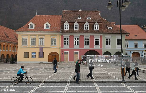 Weekend visitors relax in Sfatului square next to newlyrenovated Saxonbuilt houses in the historic district on March 9 2013 in Brasov Romania Brasov...