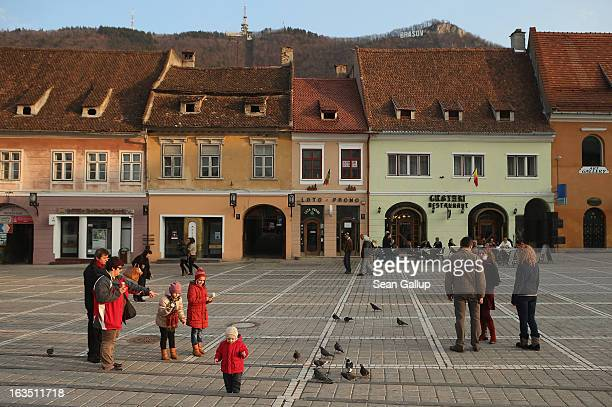 Weekend visitors relax in Sfatului square next to Saxonbuilt houses in the historic district on March 9 2013 in Brasov Romania Brasov in German...
