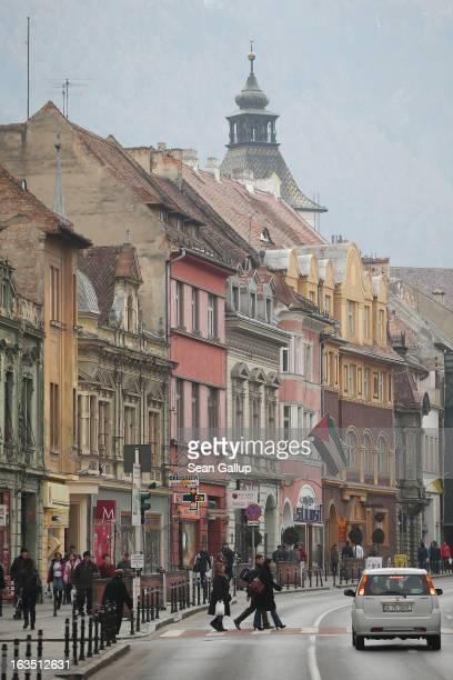Weekend visitors walk among Saxonbuilt houses in the historic district on March 9 2013 in Brasov Romania Brasov in German called Kronstadt was...