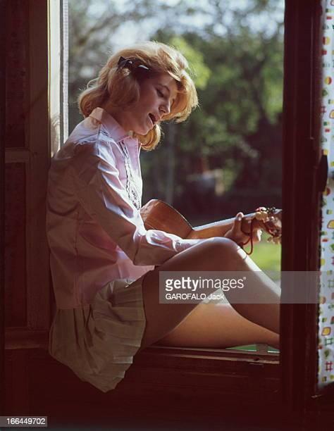 A Weekend With Sheila Attitude de SHEILA 16 ans et demi chantant en s'accompagnant à la guitare assise sur le rebord de la fenêtre dans sa maison de...