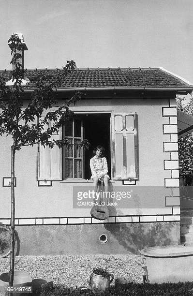 A Weekend With Sheila Attitude souriante de SHEILA 16 ans et demi posant assise sur le rebord de la fenêtre dans sa maison de BRUNOY une guitare à la...