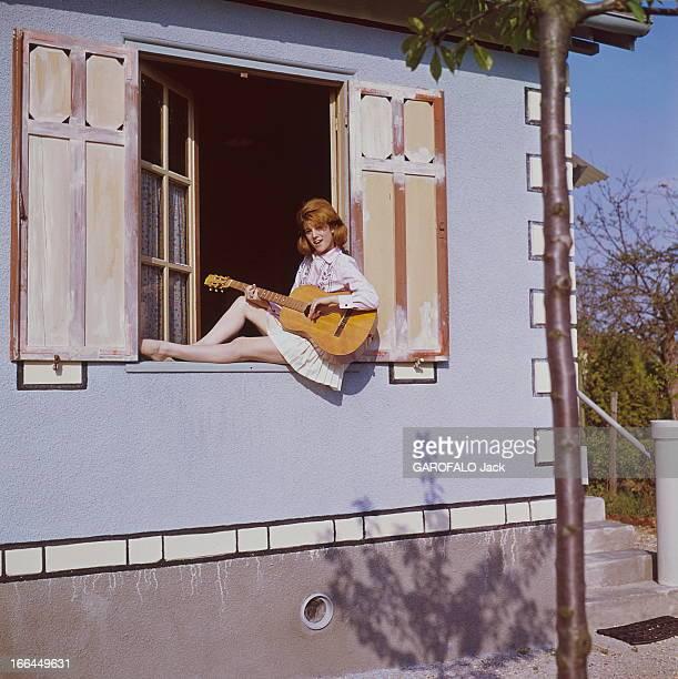 A Weekend With Sheila SHEILA 16 ans et demi chantant en s'accompagnant à la guitare assise sur le rebord de la fenêtre dans sa maison de BRUNOY