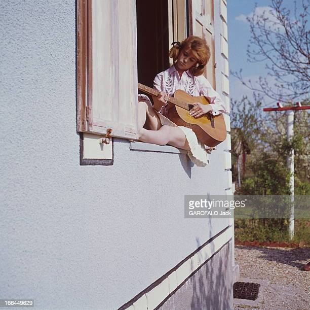 A Weekend With Sheila SHEILA 16 ans et demi jouant de la guitare assise sur le rebord de la fenêtre dans sa maison de BRUNOY