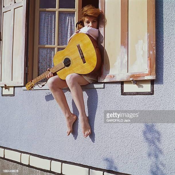 A Weekend With Sheila SHEILA 16 ans et demi posant assise sur le rebord de la fenêtre dans sa maison de BRUNOY une guitare dans les bras