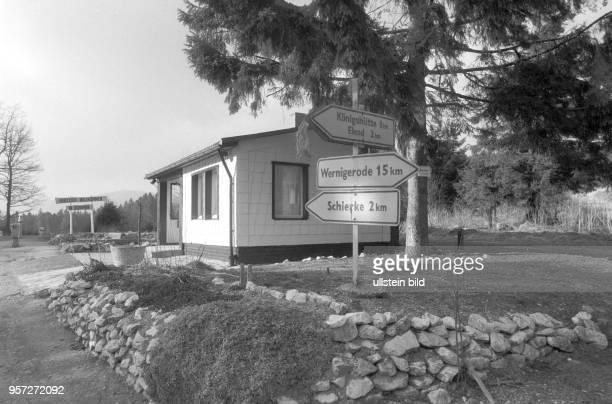 Wegweiser nach Schierke Wernigerode Königshütte und Elend stehen an vor einem kleinen Haus im Hintergrund steht ein neues Holzschild 'Willkommen in...