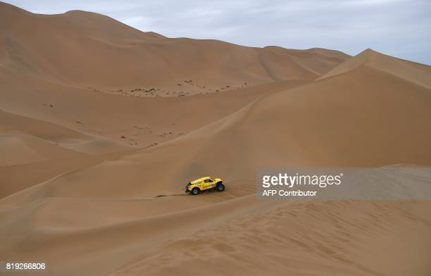 TOPSHOT Wei Han and codriver Liao Mon of China ride over sand dunes as they compete during the Stage 12 of the Silk Way 2017 between Jiayuguan and...