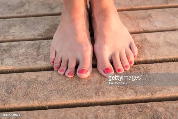Weibliche Füße mit rotem Nagellack auf sandigem Steg
