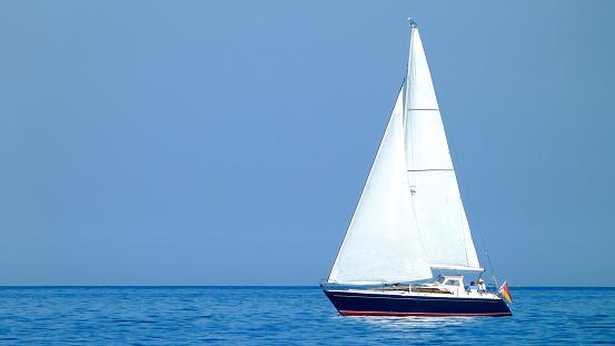 weißes Segelboot oder Yacht auf einem See oder dem Meer bei sonnigem Wetter und blauem Wasser 945106758