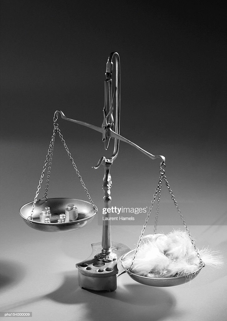 Weighing scales with feathers and weights, b&w. : Stockfoto