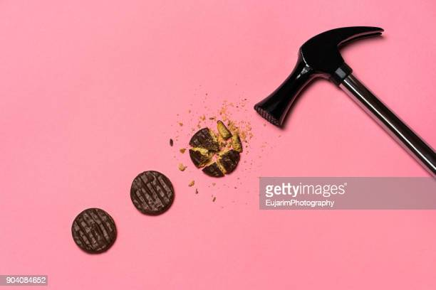 Weight loss efforts concept with broken chocolate cookies and hammer