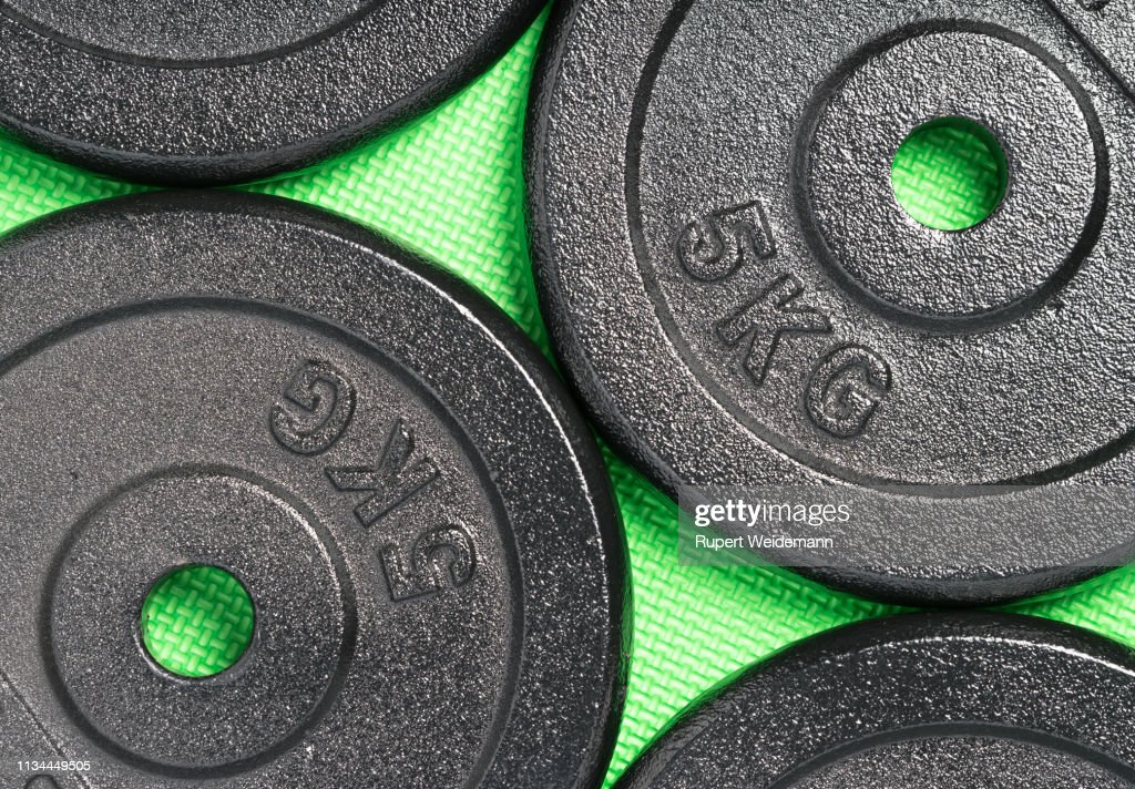 Weight plates on a colorful green weight training gym floor : Stock Photo