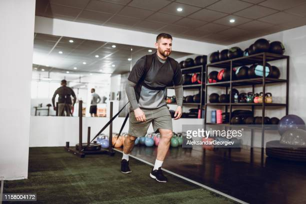 weight pulling cardiovascular training by male athlete - dragging stock pictures, royalty-free photos & images