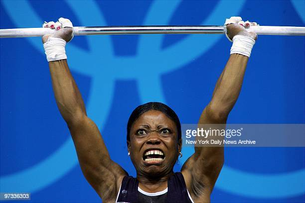Weightlifter Blessed Udoh of Nigeria competes in the 48kilogram class competition at the Nikaia Olympic Weightlifting Hall during the 2004 Summer...