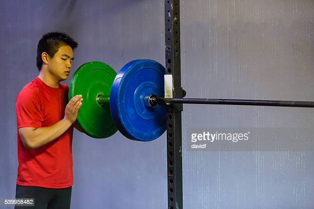 weightlifter reloads barbell weights at a cross training gym - putting stock pictures, royalty-free photos & images