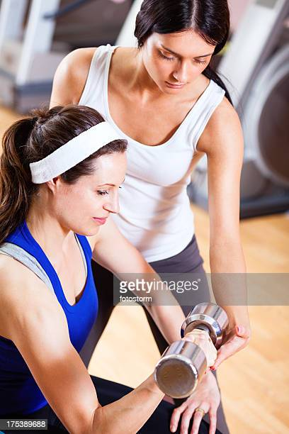 Weightlifting in gym with personal trainer