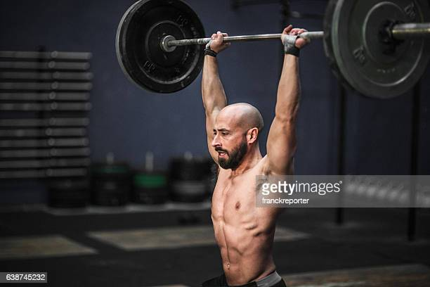 weightlifting strong man on a gym - snatch weightlifting stock photos and pictures