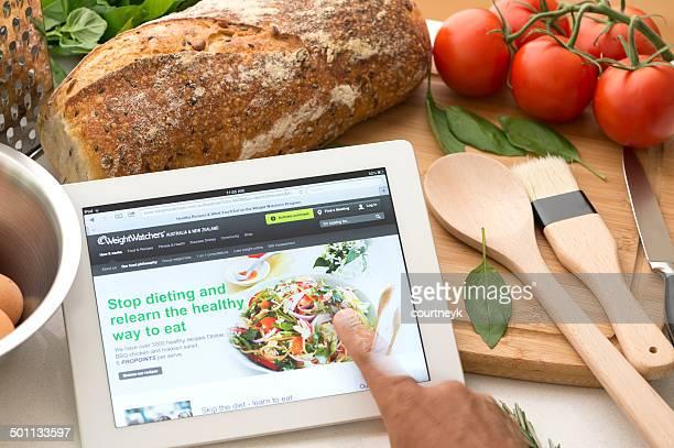 weightwatchers.com website auf einem digitalen tablet in küche - editorial stock-fotos und bilder