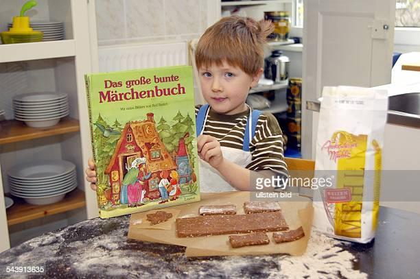 Kleiner Junge mit Märchenbuch als Vorlage für sein Lebkuchenhaus