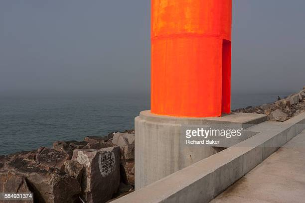 A weird landscape of the concrete fluorescentcoloured shipping navigation marker a few hundred metres out from the beach on the artificial pier on...