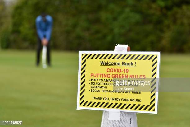 """Welcome back"""" and Covid-19 safety sign as a golfer plays on the practice putting green as golf courses reopen in England under government guidelines..."""