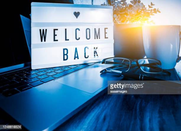 welcome back showed on light box at workspace - dorsale foto e immagini stock