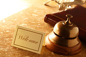 Welcome card and service bell on marble countertop in hotel