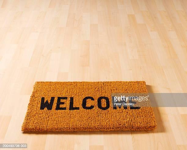 Welcome doormat on wooden floor, close-up, elevated view