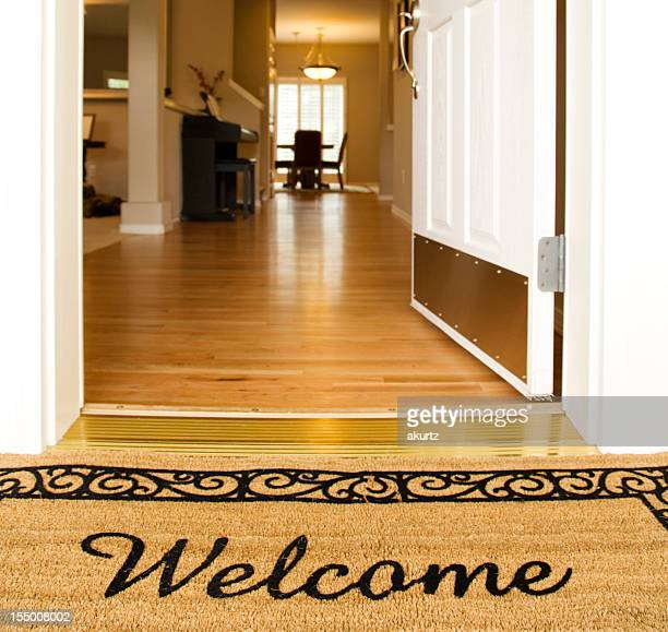 'Welcome' mat in front of white open door