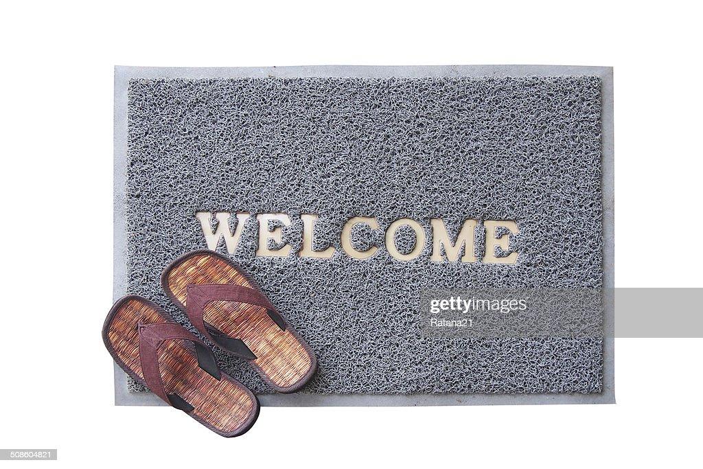 Alfombrilla marrón de bienvenida con sandalias en el suelo : Foto de stock