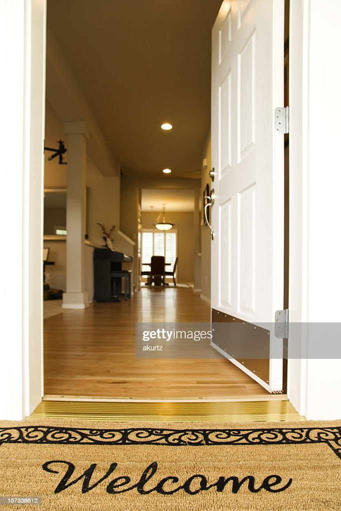 A welcome mat with the door open : Stock Photo