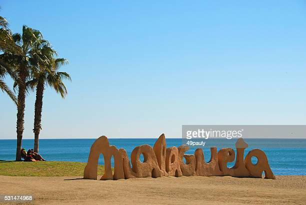 Welcome Sign of Malaga standing on the beach