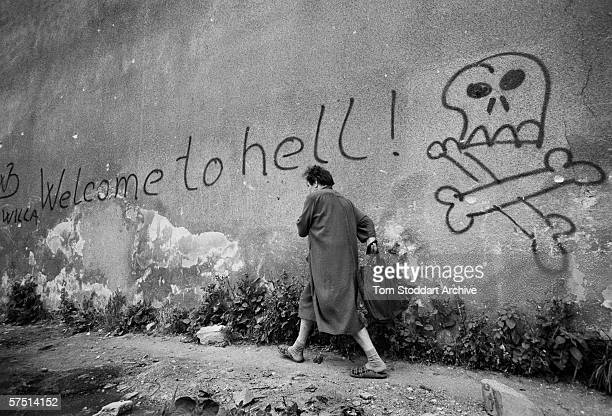 Welcome to hell - a woman hurried past graffiti in the area known as 'Sniper Alley' in Sarajevo's main thorough fare during the siege in 1992.
