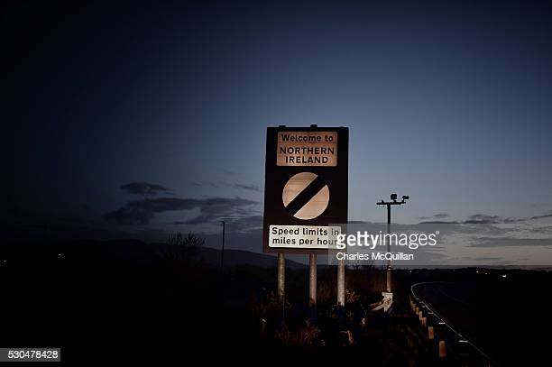 A welcome to Northern Ireland road sign indicating the change from kilometers per hour to miles per hour speed laws is illuminated by car headlights...