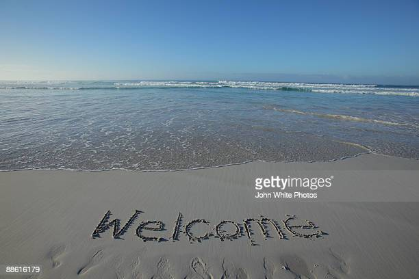 Welcome written on a clean beach