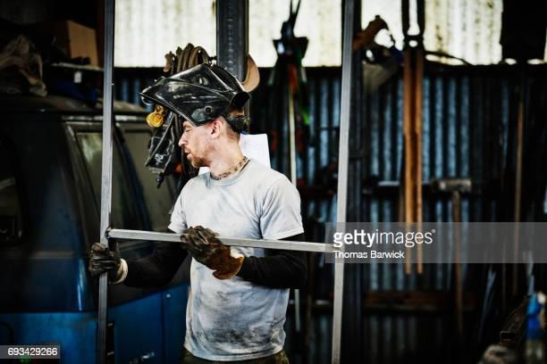 Welder checking metal frame after welding in workshop