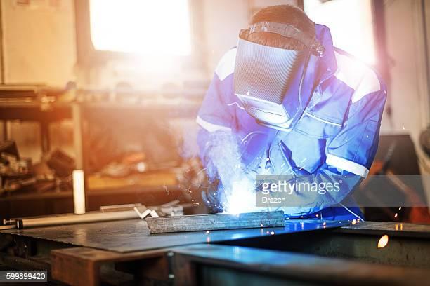 Welder in factory welding steel construction for new machine