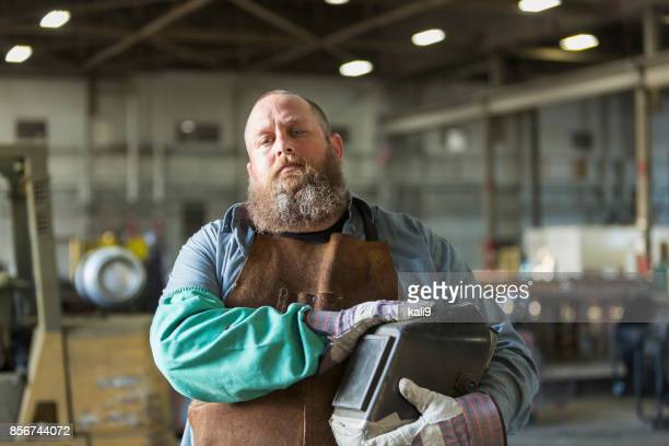 welder in metal fabrication plant - fat man beard stock photos and pictures
