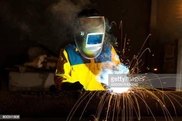 welder in the mask while working. - metal industry stock pictures, royalty-free photos & images
