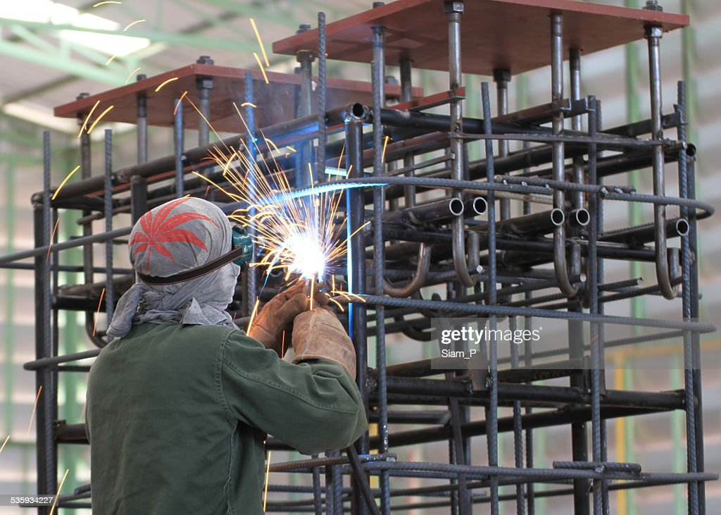 welder is welding steel frame in factory : Stock Photo