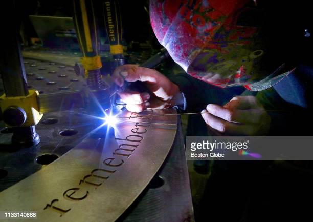 Welder John Mayer works on a weld on a seam of a large bronze circle plate that will be placed on the sidewalk near the Boston Marathon finish line...