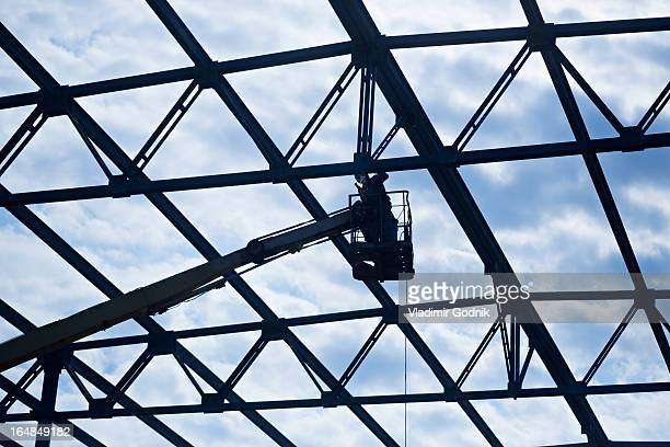Welder on crane welding roof beam