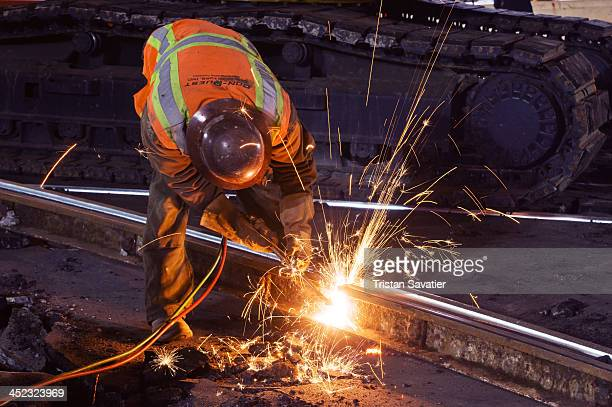 Welder using oxy-acetylene cutting torch to cut a track rail. Railroad workers were replacing a Muni light rail track section at Duboce street and...