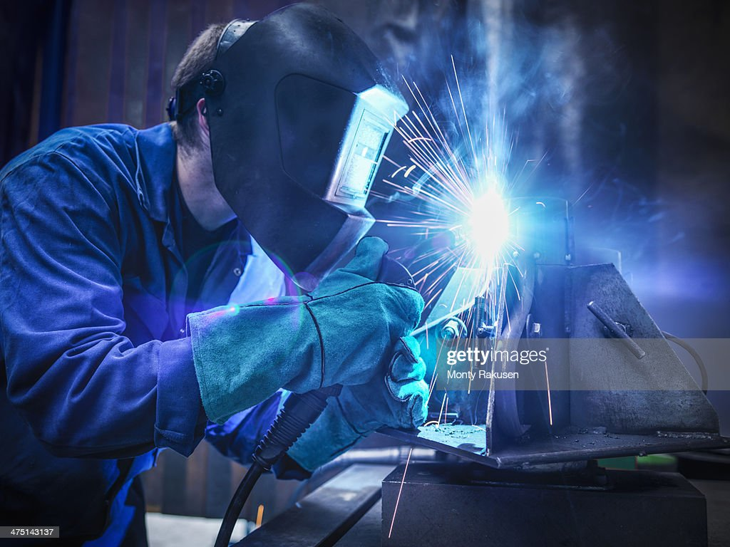 Welder wearing face mask and protective gloves in factory : Stock Photo