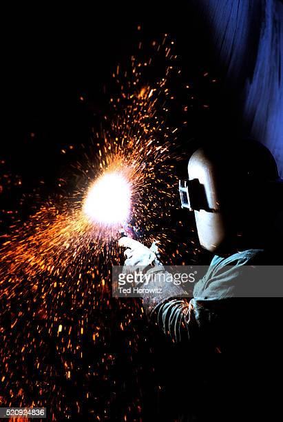 Welder welding metal pipe with a shower of sparks.