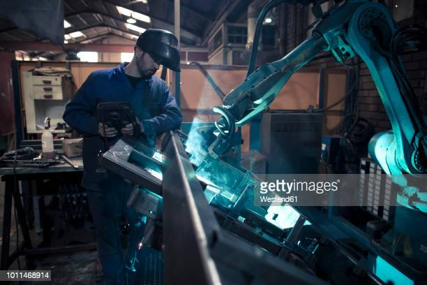 welder welding metal with robot - automation stock pictures, royalty-free photos & images