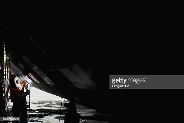 Welder welding side of boat hull in shipyard